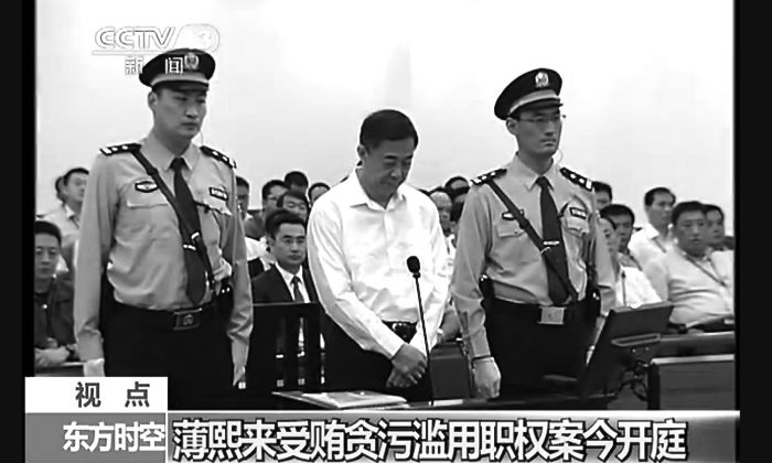 Former Politburo member Bo Xilai stands between two guards at the Jinan Intermediate Court in Shandong Province for the first day of his trial on Aug. 22. Bo's trial was negotiated to be depoliticized, according to experts.   A prosecutor urged a Chinese court to punish disgraced politician Bo with a severe sentence because of his lack of remorse over alleged corruption and abuse of power, in a trial that has offered a glimpse into the shady inner workings of China's elite. (Screenshot/Epoch Times)