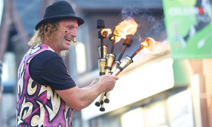 A performer invites onlookers to a playful fire display at BuskerFest. (Quincy Clark/DQC Photo)