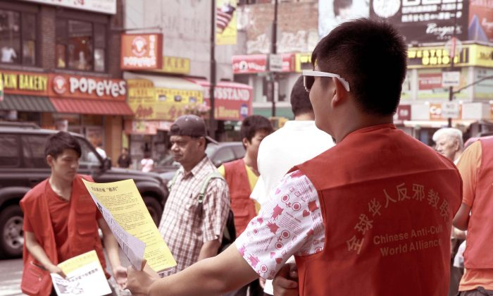 A group of 16-year-old youths try to hand the CCP's hate materials to passersby on Main Street in Flushing, Saturday, Aug. 10. (Milene Fernandez/Epoch Times)