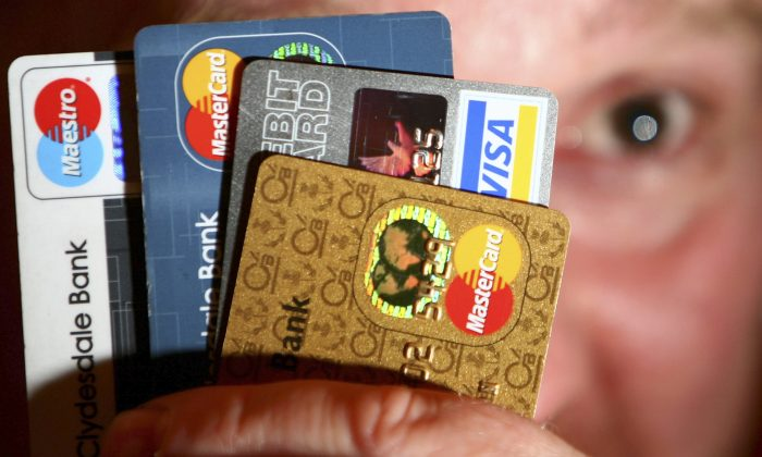 In this photo illustration a man holds up credit and debit cards. Many Americans have a wallet full of credit cars, but they have been paying them off more quickly. (Jeff J Mitchell/Getty Images)