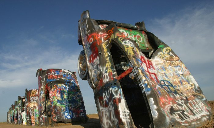 """Cars at """"Cadillac Ranch""""' on historic Route 66 in Amarillo, 06 July 2003. As a tribute to America's relationship with one of its favorite automobiles, a collective of artists called Ant Farm in 1974 placed 10 Cadillacs, ranging from a 1949 Club Coupe to a 1963 Sedan, in a wheat field located west of Amarillo. (Robyn Beck/AFP/Getty Images)"""