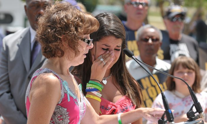 Jane Dougherty (L) and Carlee Soto read the names of victims at a remembrance ceremony in Aurora, Colo on July 9. Both women's sisters were killed during the Sandy Hook Elementary mass shooting. The event was supported by the No More Names tour. (Tom Cooper/Getty Images)