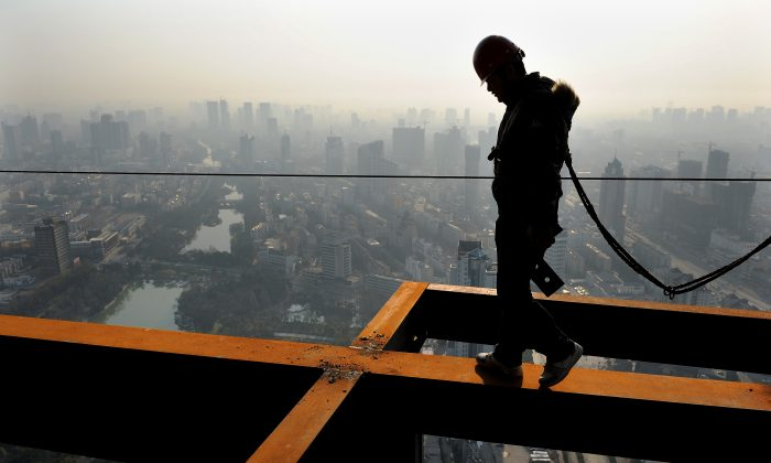 A Chinese worker makes his way along a beam at a construction project in Hefei, east China's Anhui province on April 14, 2011. Despite policy attempts to take some steam off the housing market, property prices have continued to grow. (STR/AFP/Getty Images)