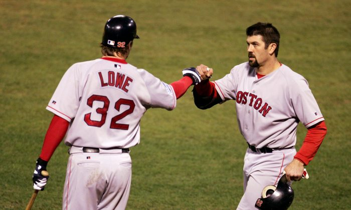 Jason Varitek (R) of the Boston Red Sox is congratulated by teammate Derek Lowe after scoring against the St. Louis Cardinals during the third inning of Game 4 of the World Series on Oct. 27, 2004 at Busch Stadium in St. Louis. Varitek and Lowe were acquired by Boston at the trade deadline in 1997 for Heathcliff Slocum in a deal Seattle surely wishes it could have back. (Al Bello/Getty Images)