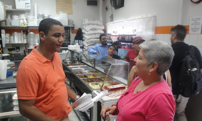 Pablo Martinez talks to Councilwoman Maria del Carmen Arroyo at his restaurant, the Dominican Restaurant, on East 156th St. in the Bronx, Aug. 30, 2013. Martinez is concerned about how much money a proposed ban on polystyrene containers and packaging would cost his business. (Sarah Matheson/Epoch Times)