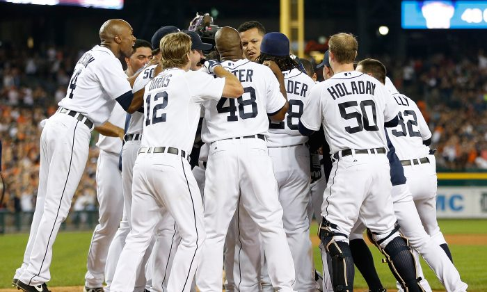 Miguel Cabrera #24 of the Detroit Tigers gets mobbed at home plate after hitting a ninth inning walk off home run to beat the Kansas City Royals 6-5 at Comerica Park on August 17, 2013 in Detroit, Michigan. (Gregory Shamus/Getty Images)