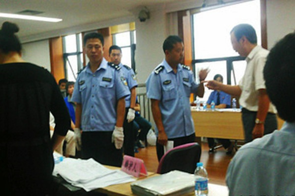 Bailiffs in blue block lawyers attempting to leave the courtroom to see Cheng Hai, who was taken out and beaten by other bailiffs, after getting into a dispute with a judge. (Weibo.com)