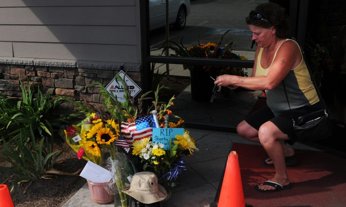 Lill Duncan takes a photo on Aug. 22, 2013, of a memorial for Delbert Belton, an 88-year-old World War II veteran who was beaten to death, in Spokane, Wash. (AP Photo/The Spokesman-Review, Tyler Tjomsland)