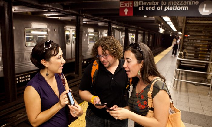 Kirsten Mickelson (R), Ben Abo (C), and Amy Coren use their cellphones at the 14th Street A train station on Sept. 27, 2011. (Samira Bouaou/Epoch Times)