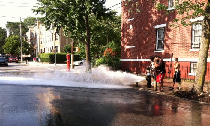 An illegally opened fire hydrant in Brooklyn in July. Legally opened fire hydrants use only about 25 gallons a minute, versus 1,000 gallons a minute for illegally opened hydrants. (Genevieve Belmaker/Epoch Times)