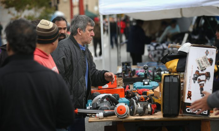 Shoppers look over tools being offered for sale by a vendor at the Maxwell Street Market in Chicago, Illinois in this file photo. The underground economy exists as separate economy that competes and complements the official economy in the provision of workers and resources. (Scott Olson/Getty Images)