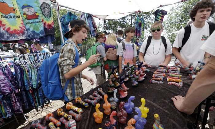 A group of teenaged boys look over a display of glass pipes at the first day of Hempfest in Seattle, Friday, Aug. 16, 2013. (AP Photo/Elaine Thompson)