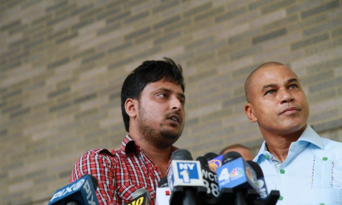 Faysal Kabir Mohammad Himon, the driver involved in the gruesome accident that severed a British tourist's foot  on August 21, stands beside Fernando Mateo, head of the New York State Federation of Taxi Drivers, outside Bellevue hospital, on Aug. 23. Sian Green, the woman who lost her leg in the accident, is being treated at the hospital. (Ivan Pentchoukov/Epoch Times)