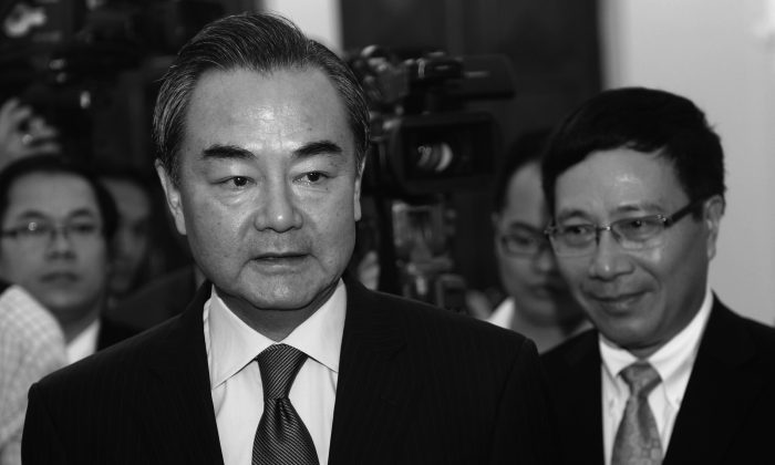 Chinese Foreign Minister Wang Yi (C) in Vietnam on Aug. 4, 2013. Wang said that China keeps a close eye on Syria; state media recently warned the United States from a military intervention, after the use of chemical weapons was reported. (Hoang Dinh Nam/AFP/Getty Images)