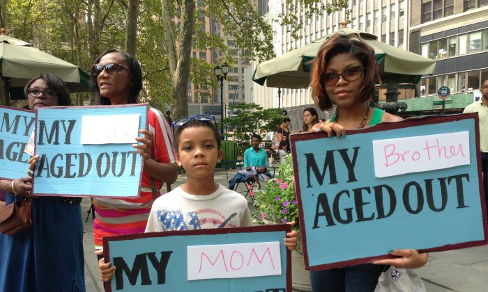 Anthea Nesbitt, 29, and her son, Antonio Nesbitt, 8, hold signs at Bryant Park, New York City, Aug. 30, 2013. (Ivan Pentchoukov/Epoch Times)