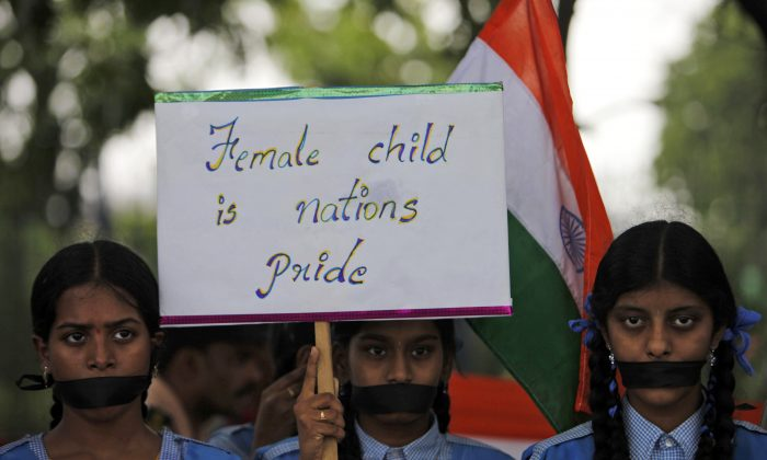 Indian schoolgirls hold a placard and participate in a silent rally in Hyderabad, India, on April 23, 2013, against the rape of a 5-year-old girl in New Delhi. The case brought a new wave of protests against how Indian authorities handle such crimes. (AP Photo/Mahesh Kumar A.)