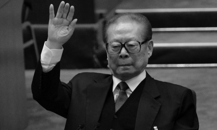 Former Chinese Communist Party head Jiang Zemin raises his hand at the closing of the 18th Communist Party Congress at the Great Hall of the People in Beijing on Nov. 14, 2012. The aged Jiang recently had dinner with former U.S. Secretary of State Henry Kissinger in an effort to shore up his waning influence, writes Xia Xiaoqiang. (Goh Chai Hin/AFP/Getty Images)