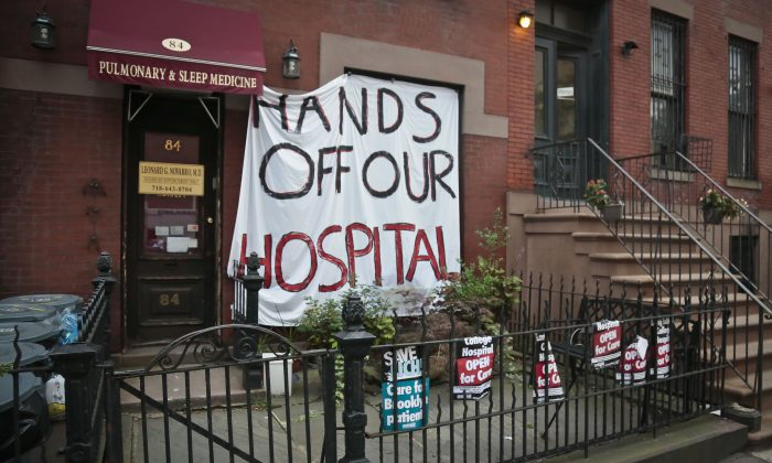 A large sign hangs over the front of a brownstone, supporting Long Island College Hospital (LICH) to remain open, Tuesday, July 23 in Brooklyn. Nurses, doctors and health care workers' unions continue to hold protest rallies and have sued to stop possible plans to close LICH, a teaching hospital. (Bebeto Matthews/AP)