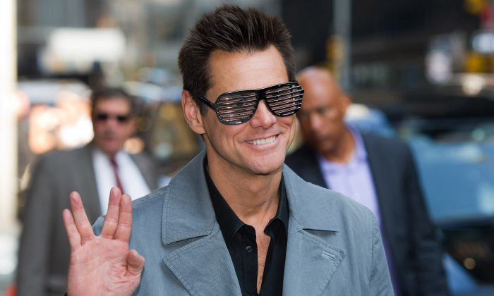 """Jim Carrey leaves a taping of the """"Late Show with David Letterman"""" in New York, July 4, 2013. """"Kick-Ass 2"""" director Jeff Wadlow defended his film on Tuesday Aug. 6, 2013 after star Jim Carrey chose not to support the action comedy because of its violence. Carrey, who plays vigilante Colonel Stars and Stripes in the sequel to the 2010 hit, has distanced himself from the film, saying the shooting massacre at Connecticut's Sandy Hook Elementary school changed his perspective. (AP Photo/Charles Sykes)"""