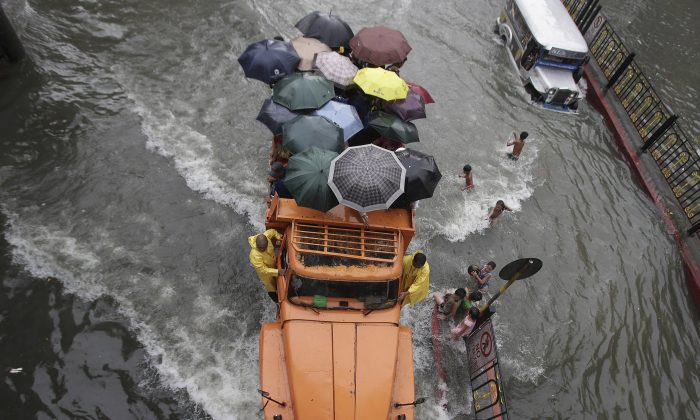 A truckload of stranded commuters cross a flooded street in Manila, Philippines Monday, Aug. 19, 2013. Torrential rains brought the Philippine capital to a standstill Monday, but the waters began to recede Tuesday. (AP Photo/Aaron Favila)