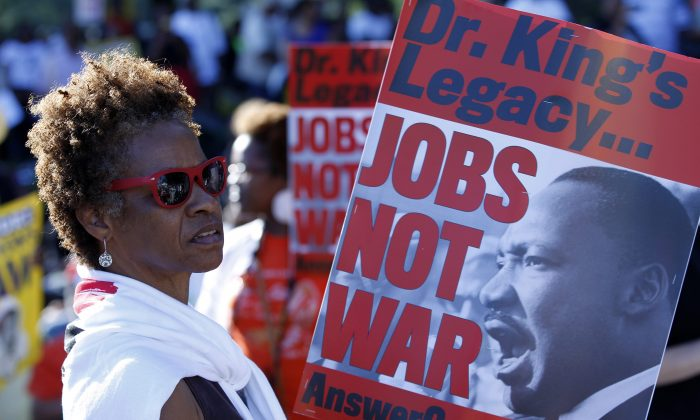 Claudia Hanes from Kentucky holds a placard during a rally to commemorate the 50th anniversary of the 1963 March on Washington at the Lincoln Memorial in Washington, Saturday, Aug. 24, 2013. (AP Photo/Jose Luis Magana)