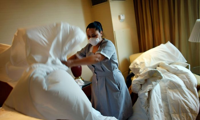 A maid changes sheets in a hotel room. A new do-it-yourself bedbug trap may help keep hotel rooms safer for visitors—human visitors. (Joe Raedle/Getty Images)