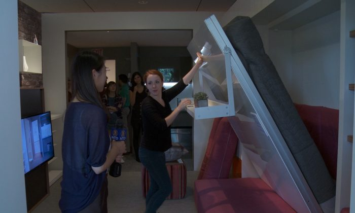 Emily Theakston, an intern at the Museum of the City of New York, puts away the Murphy bed in a micro-apartment exhibit at the museum. Theakston and another museum intern, Taylor Jones (not pictured), are one of a series of volunteers who are living in the apartment for 24 hours. (NTDTV)