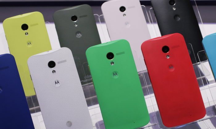 Motorola Moto X smartphones, using Google's Android software, are shown, Thursday, Aug. 1, 2013 at a press preview in New York. The back of the phone is available in 18 colors. (AP Photo/Mark Lennihan)