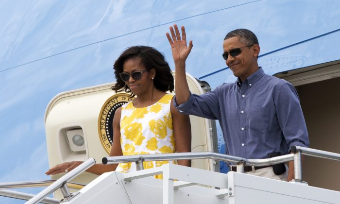 President Barack Obama and first lady Michelle Obama wave as they arrive in Cape Cod, Mass., on Aug. 10, 2013. (AP Photo/Jacquelyn Martin)