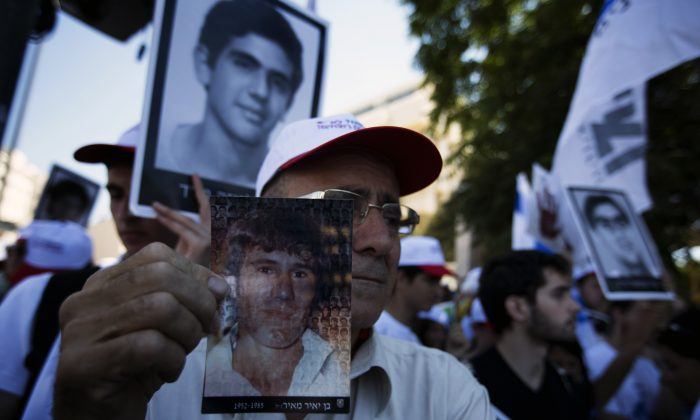 Israelis holding pictures of their loved ones, killed by Palestinians, protest against the planned release of 104 veteran Palestinian and Israeli-Arab prisoners in front of the Prime Minister's office in Jerusalem on July 28, 2013. (Menahem Kahana/AFP/Getty Images)