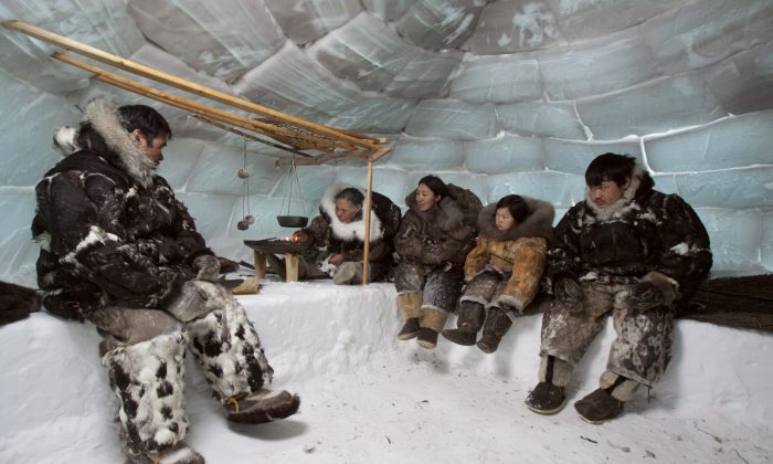 """Traditional igloo life on the Belcher Islands, where eider duck clothing was the key to keeping warm. For the first time in many years, three generations are wearing traditional clothing, created for the documentary """"People of a Feather."""" (Joel Heath)"""