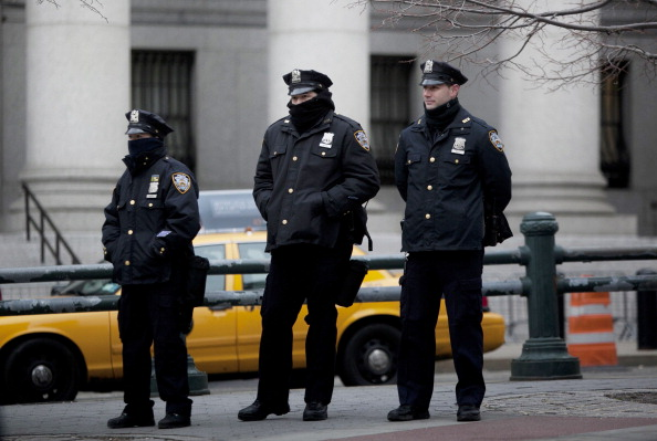 """New York CIty Police officers stand near a demonstration against the city's """"stop-and-frisk"""" searches in lower Manhattan near Federal Court, New York, March 18, 2013. (Allison Joyce/Getty Images)"""