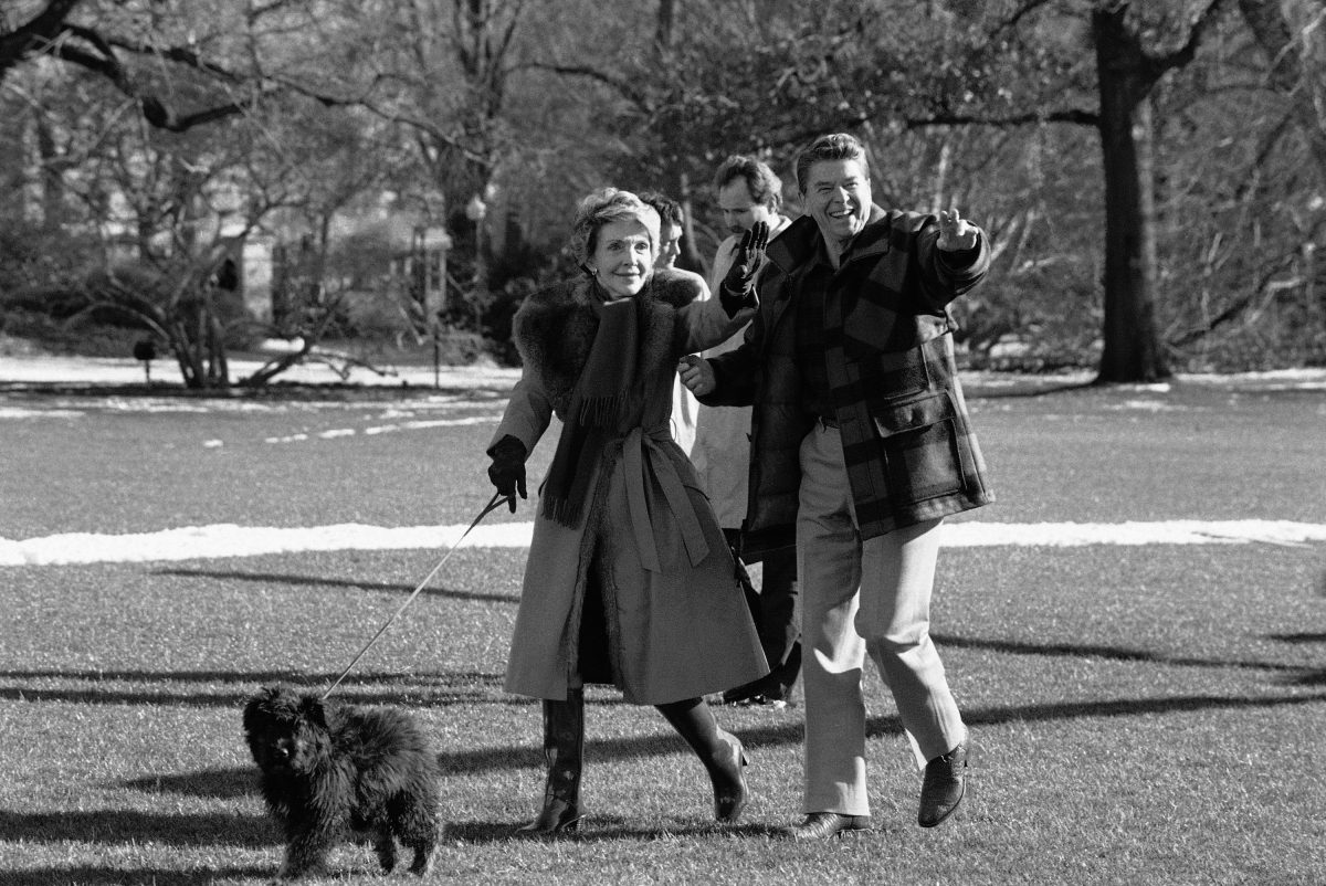 President Ronald Reagan and first lady Nancy Reagan wave after they arrived back on Sunday, Jan. 13, 1985 at the White House in Washington with their dog Lucky, a Bouvier des Flandres. (AP Photo/Ron Edmonds)