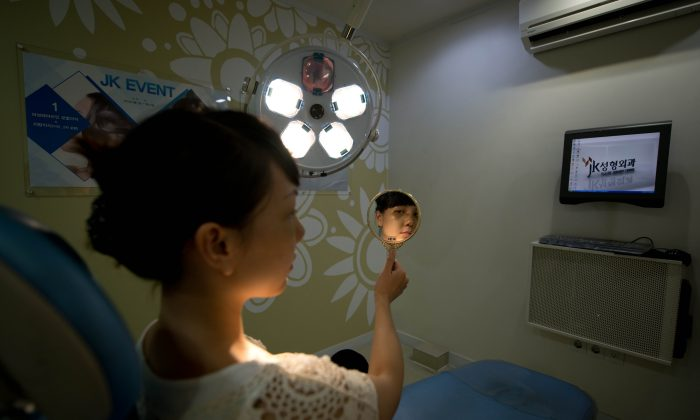 A Vietnamese-American patient checks her appearance four days after undergoing a cosmetic rhinoplasty and eye procedures at the JK Medical Group plastic surgery hospital in Seoul, South Korea on July 15, 2013. Skilled plastic surgeons in looks-obsessed South Korea are enjoying an unexpected boom as increasing numbers of foreigners seek aesthetic absolution in what is fast becoming the cosmetic procedure capital of the world. (Ed Jones/AFP/Getty Images)