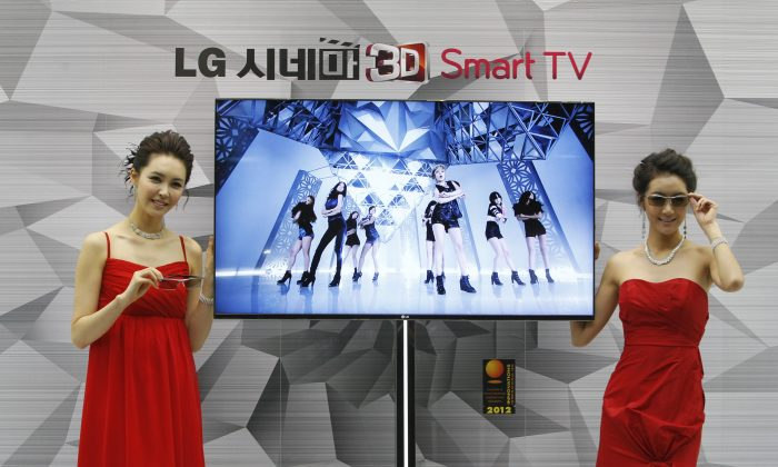 South Korean models pose with a CINEMA 3D Smart TV during a press conference to introduce the LG Electronics' television and the company's marketing strategy for 2012 in Seoul, South Korea, Thursday, Jan. 19, 2012. New York Senator Charles Schumer warned on Sunday that hackers can access these cameras and spy on people in their homes, and sent a letter to TV manufacturers urging them to create uniform security standards for Smart TVs. (AP Photo/Ahn Young-joon)