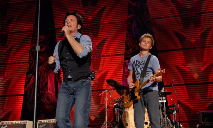 Musician John Mellencamp (L) performs with his band and his son Speck (R), during the Farm Aid Concert event in St. Louis, Sunday, Oct. 4, 2009. (AP Photo/Kyle Ericson)