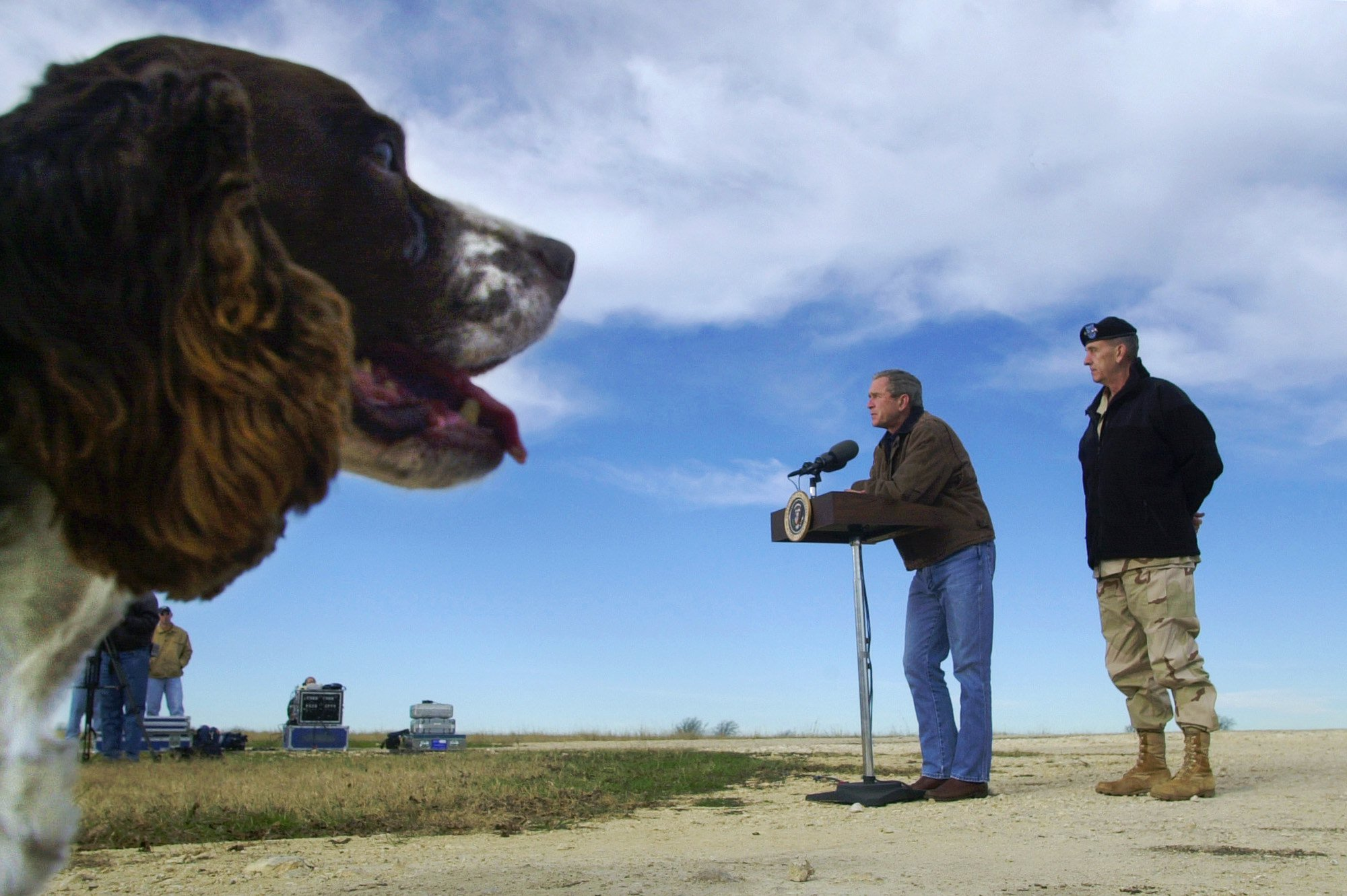With his dog Spot, an English Springer Spaniel, looking on, President Bush, standing with Afghan war commander Army Gen. Tommy Franks, answers questions during a news conference at his ranch in Crawford, Texas, Friday, Dec. 28, 2001. (AP Photo/Susan Walsh)