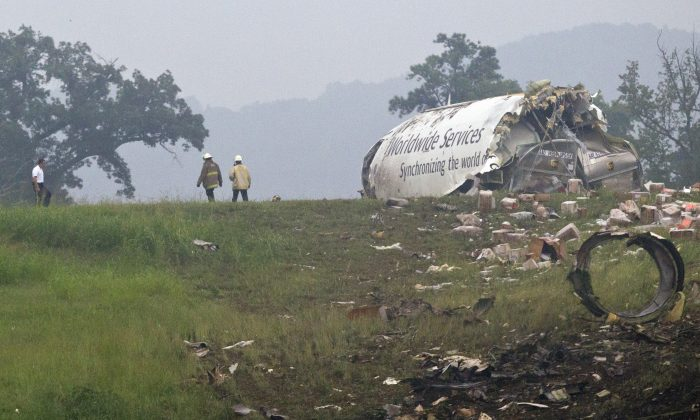 Fire crews investigate where a UPS cargo plane lies on a hill at Birmingham-Shuttlesworth International Airport, in Birmingham, Ala. after crashing on approach on Wednesday, Aug. 14, 2013. (AP Photo/Butch Dill)
