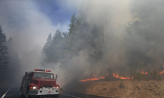 A fire truck drives past burning trees as firefighters continue to battle the Rim Fire near Yosemite National Park, Calif., on Monday, Aug. 26, 2013. Crews working to contain one of California's largest-ever wildfires gained some ground Monday against the flames threatening San Francisco's water supply, several towns near Yosemite National Park and historic giant sequoias. (AP Photo/Jae C. Hong)