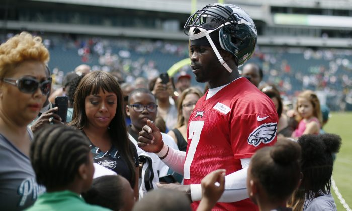 Philadelphia Eagles quarterback Michael Vick signs autographs at the NFL football team's training camp in Philadelphia Monday, Aug. 26, 2013. (AP Photo/Matt Rourke)