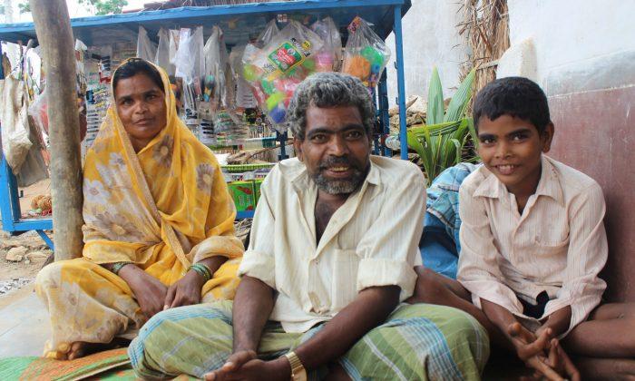 Chaman Shab sits with his family in front of his business cart in Benakanakonda village in Karnataka State, India, on July 26, 2013 (Venus Upadhayaya/Epoch Times)