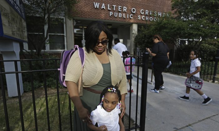 """Jennifer Press stands outside on the first day of classes at Gresham Elementary, July 26, in Chicago. Thousands of students will walk to school along newly designated """"Safe Passage"""" routes. (AP Photos/M. Spencer Green)"""