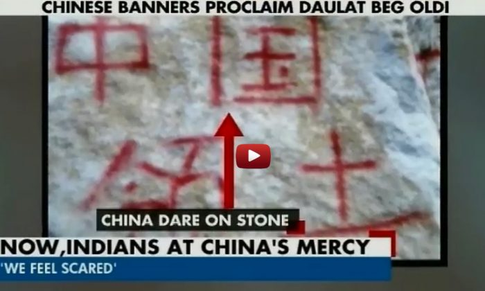 """A screenshot from the Indian news channel Headlines Today shows a stone said to be in Indian territory on which is painted in Chinese characters """"Chinese territory."""" Chinese soldiers have reportedly prevented Indian troops from patrolling in Indian territory 19 times since April, including once last week.(Epoch Times)"""