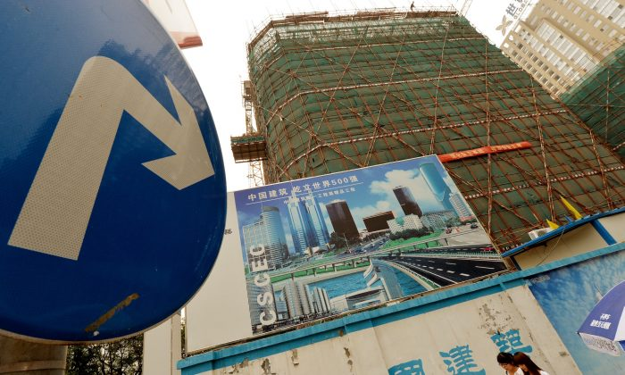 Chinese commuters walk past property development billboards in the Central Business District in Beijing on July 26, 2013. Local governments around China are worried about the investigation into their debt being organized now by central authorities. (Mark Ralston/AFP/Getty Images)