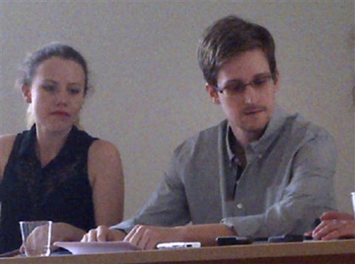 In this image provided by Human Rights Watch, NSA leaker Edward Snowden, center, attends a news conference at Moscow's Sheremetyevo Airport with Sarah Harrison of WikiLeaks, left, Friday, July 12, 2013.  (AP Photo/Human Rights Watch, Tanya Lokshina, File)