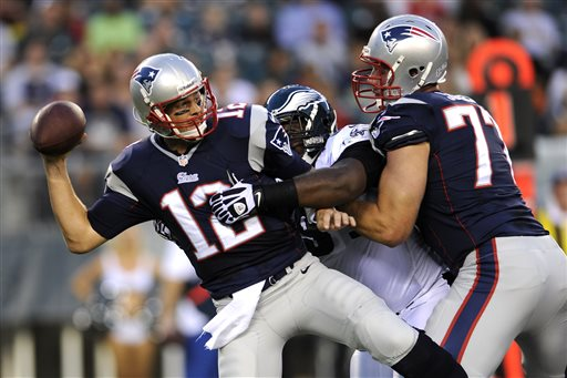 New England Patriots quarterback Tom Brady, left, tries to pass the ball as Philadelphia Eagles defensive tackle Fletcher Cox, center, breaks past Patriots tackle Nate Solder during the first half of a preseason NFL football game on Friday, Aug. 9, 2013, in Philadelphia. (AP Photo/Michael Perez)