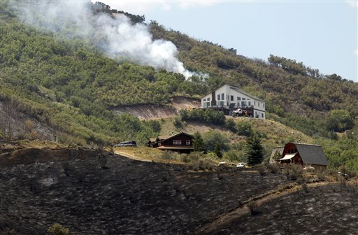 A hot spot flares up above homes in Rockport Estates in Wanship, Utah, Wednesday, Aug. 14, 2013. The lightning-sparked blaze was among several in the West where fires have devoured dry grass and brush and burned to the edges of small communities. (AP Photo/The Salt Lake Tribune, Al Hartmann)