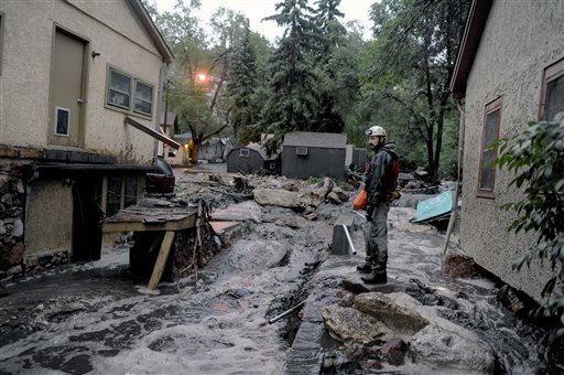 Volunteer rescuer Jesse Rochette searches the Fountain Creek flood waters for anyone trapped or stranded as another flash flood washes off the Waldo Canyon burn scar, Friday, Aug. 9, 2013 in Manitou, Colo. Another missing person was accounted for. (AP Photo/The Colorado Springs Gazette, Michael Ciaglo)