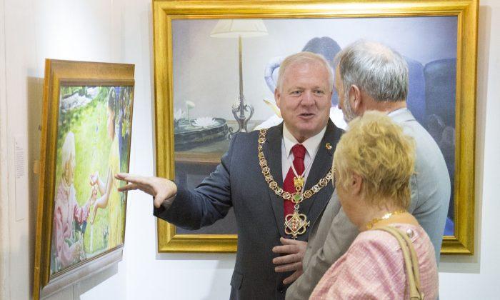 The Mayor of Caernarfon Roy Owen talks to Eddie Aitken, Director of Zhen Shan Ren Arts (UK), in front of the painting 'The Gift' by Kathleen Gillis. (Simon Gross/Epoch Times)