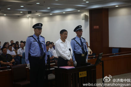 In most photos of Bo Xilai when he was official, he looked much taller than the people around him. In the courtroom, defendant Bo is flanked by two guards. Note the tall stature of the guards relative to Bo. These guards are carefully selected to create a public impression.  (Weibo of Jinan Court)